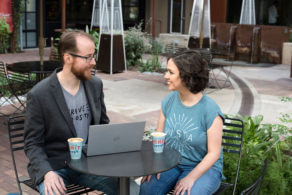 Megan and Travis face each other while working at an outdoor coffee shop