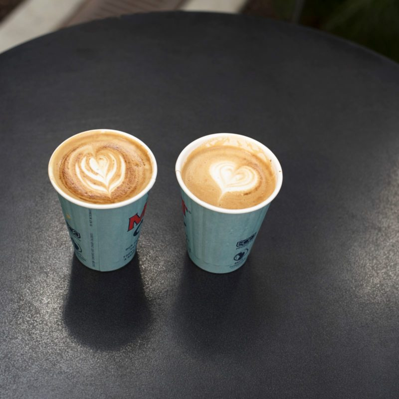 Two cappuccinos in blue to-go cups on top of a black cafe table