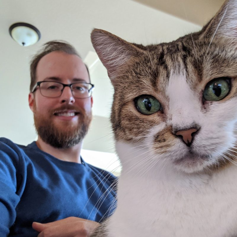 Travis sits on the couch with his cat Sadie on his lap. Sadie is directly facing the camera