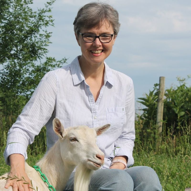 Deborah sits with a white goat at her farm. She is facing the camera and smiling