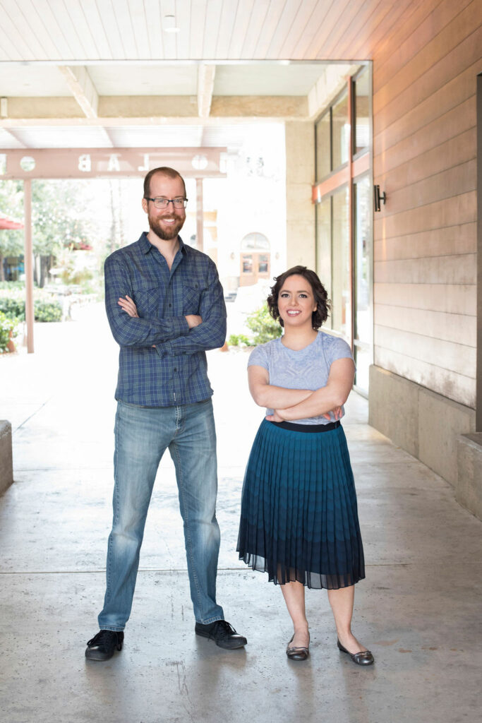 Travis and Megan stand side by side in a covered space outdoors