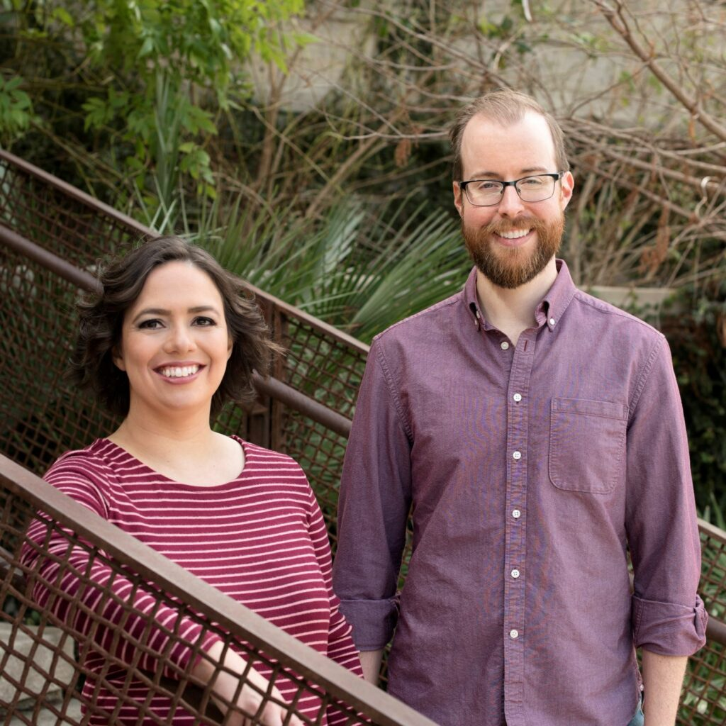 Megan and Travis stand side by side facing the camera on an outdoor staircase