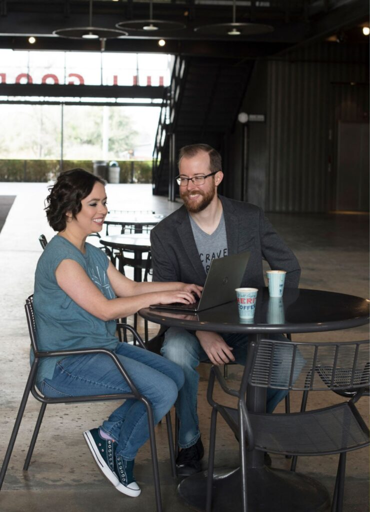 Megan and Travis work on a shared laptop in an industrial space